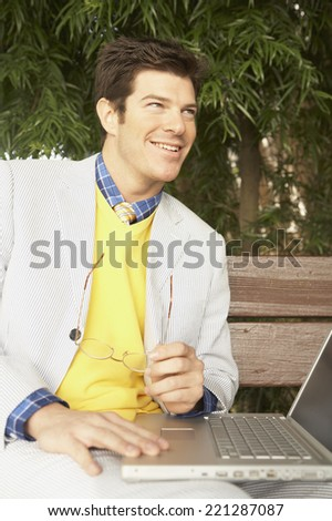 Businessman with laptop outdoors - stock photo
