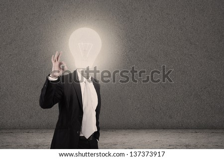 Businessman with light bulb head showing OK sign - stock photo