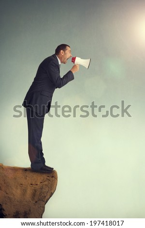 businessman with loudhailer on the edge of a cliff shouting - stock photo