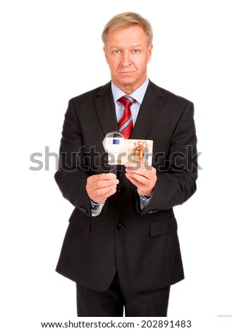 Businessman with magnifier and euro - stock photo