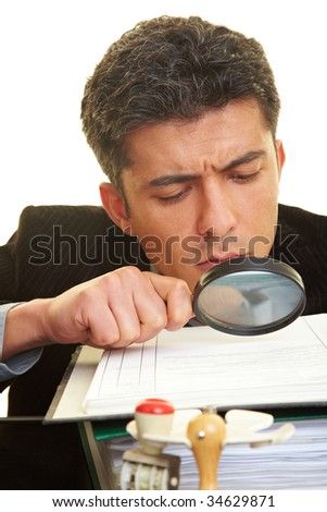 Businessman with magnifying glass reading the fineprint in a contract - stock photo