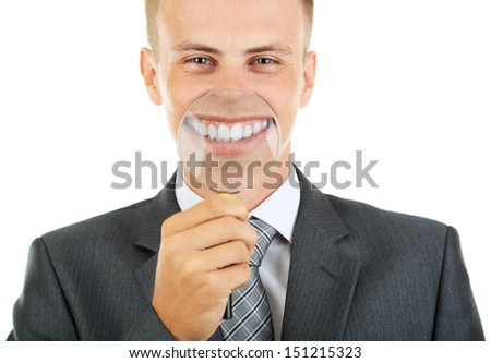 Businessman with magnifying glass zooming on his smile - stock photo