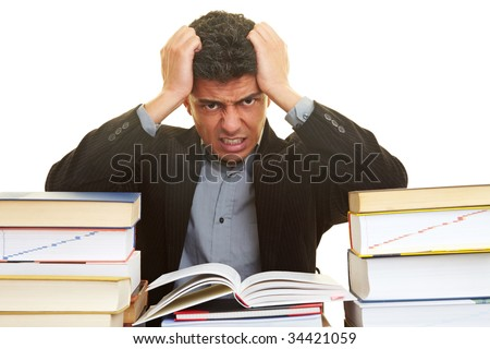 Businessman with many books pulling his hair - stock photo