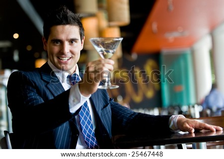 Businessman with martini in a bar - stock photo