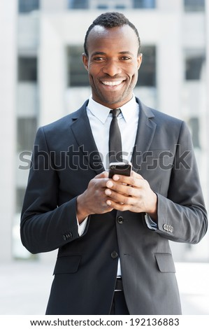 Businessman with mobile phone. Cheerful young African man in formalwear holding mobile phone and smiling while standing outdoors - stock photo