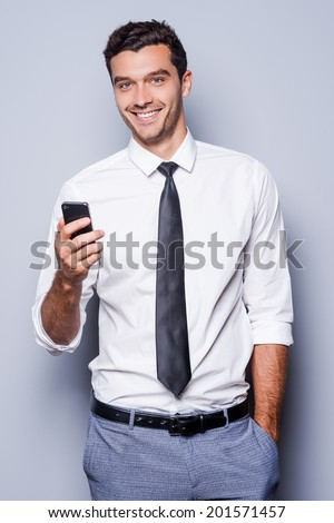 Businessman with mobile phone. Confident young man in shirt and tie holding mobile phone and smiling while standing against grey background  - stock photo