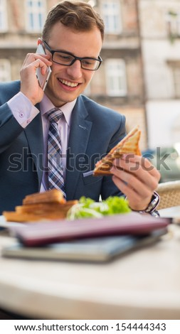 Businessman with mobile phone during breakfast. - stock photo