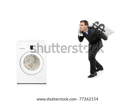 Businessman with money bag on his back going towards a washing machine isolated on white - stock photo