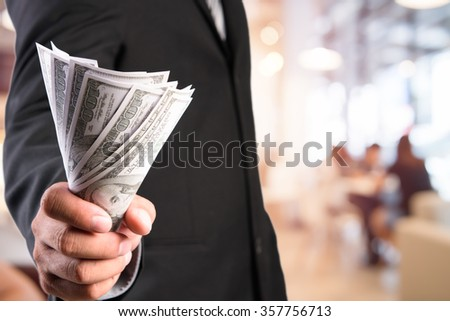 Businessman with money in hand, US dollar (USD) bills - investment, success and profitable business concepts - stock photo