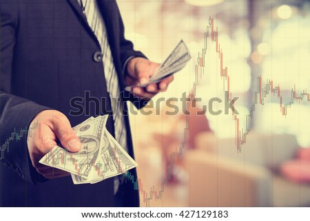 Businessman with money in hand, US dollar (USD) bills - investment, success and profitable business concepts.with stock chart, investment concept. - stock photo