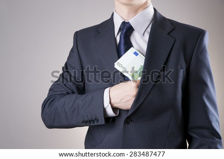 Businessman with money in studio on a gray background - stock photo