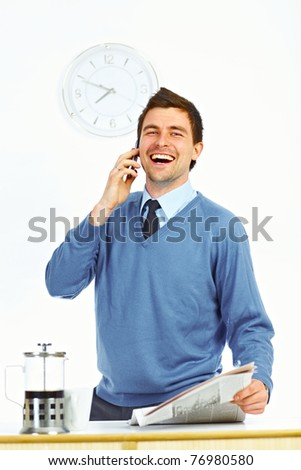 Businessman with newspaper in kitchen talking by cell phone and laughing - stock photo