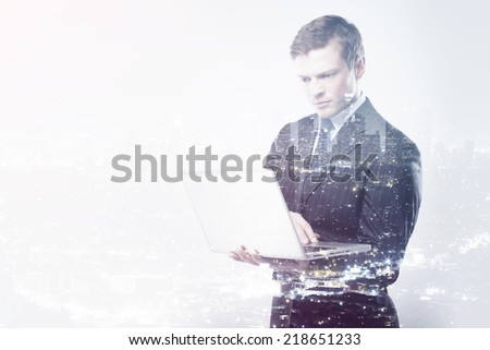businessman with nonebook on a city background - stock photo