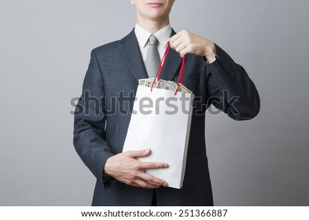 Businessman with package full of money in the hands of on gray background - stock photo