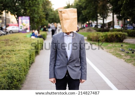Businessman with paper bag on the head in the street - stock photo