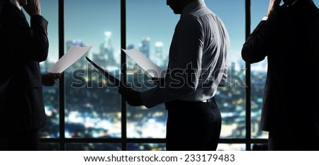 businessman with paper working in night office - stock photo