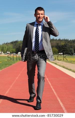 businessman with phone and laptop on a running track - stock photo