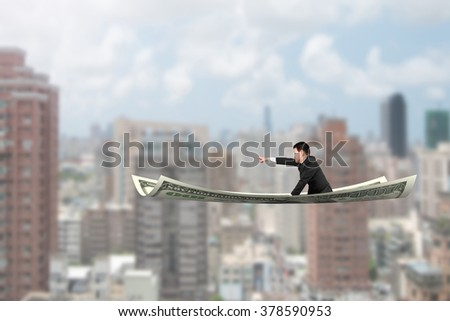 Businessman with pointing finger gesture sitting on money flying carpet, with city buildings background. - stock photo