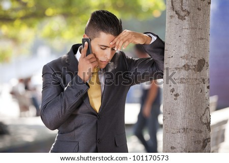 businessman with problems talking at his cellphone next to a tree - stock photo