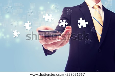 Businessman with puzzle over cellphone on light blue background - stock photo