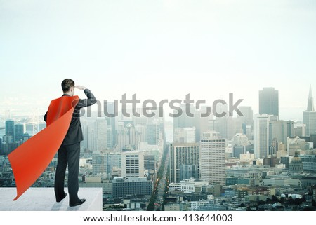 Businessman with red superhero cape standing on pedestal and looking into the distance on cityscape background - stock photo