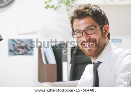 Businessman with rimmed glasses working./ Young businessman in office looking at camera.  - stock photo