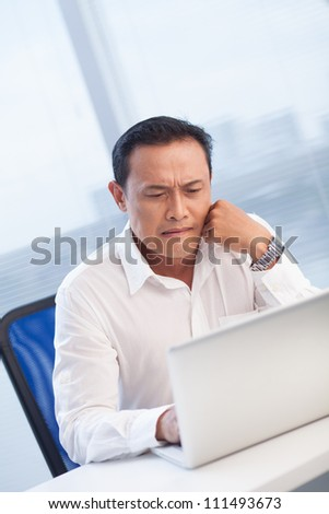 Businessman with serious look using laptop at office - stock photo