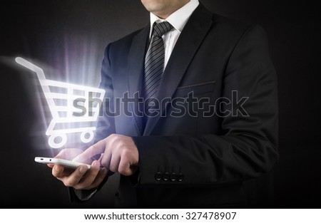 Businessman with shopping cart on smart phone        - stock photo