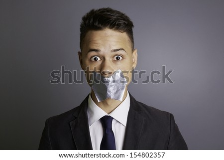 Businessman with silver tape over his mouth, conceptual image, restriction, silence, frightens, eyes wide open, formal, isolated on gray background, studio shoot. - stock photo