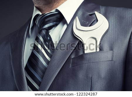 Businessman with spanner in suit pocket - stock photo