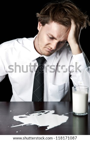 Businessman with spilled glass of milk, desaturated with black background - stock photo