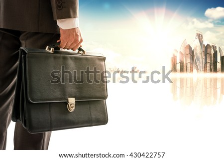 Businessman with suitcase against modern city, rear view - stock photo