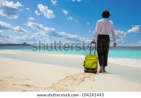 Businessman with suitcase walking on the beach towards sea - stock photo