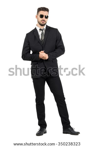 Businessman with sunglasses holding clasped hands. Full body length portrait isolated over white studio background. - stock photo