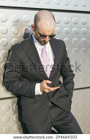 Businessman with sunglasses using his phone leaning on a metal wall - stock photo