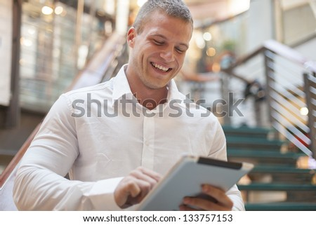 Businessman with tablet computer in hands, blurred background, modern business building - stock photo