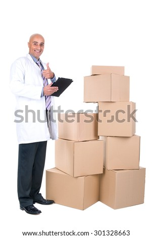 Businessman with tablet posing near a stack of cardboard boxes - stock photo