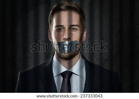 Businessman with tape over his mouth - stock photo
