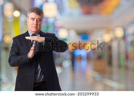 businessman with time out gesture in a shopping center - stock photo