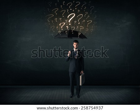 Businessman with umbrella and a lot of drawn question marks concept on background - stock photo