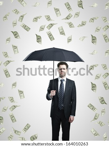 businessman with umbrella and dollars rain - stock photo
