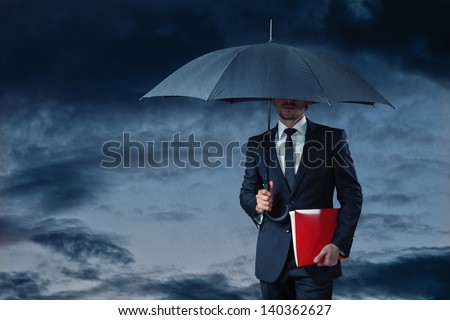 businessman with umbrella in stormy weather holding red folder - stock photo