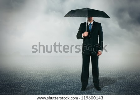 Businessman with umbrella standing at cloudy background - stock photo