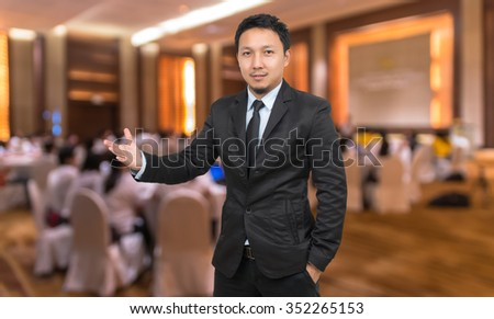 Businessman with welcoming gesture on Abstract blurred photo of conference hall or seminar room with attendee background, business concept - stock photo