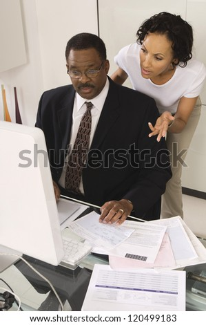 Businessman with woman gesturing while looking at computer at desk in office - stock photo
