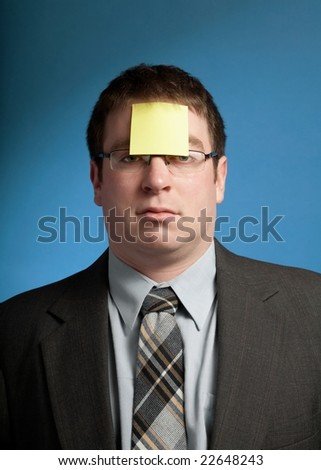 Businessman with yellow sticky note on forehead - stock photo