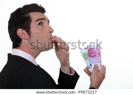 Businessman wondering what to do with his money - stock photo