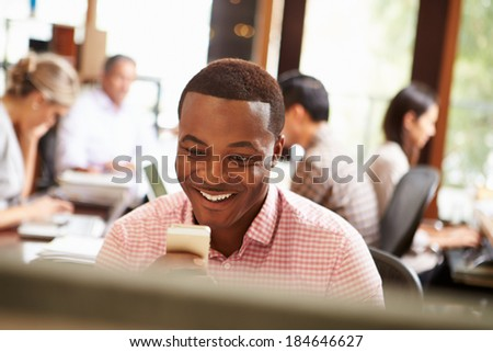 Businessman Working At Desk Using Mobile Phone - stock photo