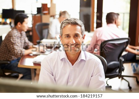 Businessman Working At Desk With Meeting In Background - stock photo