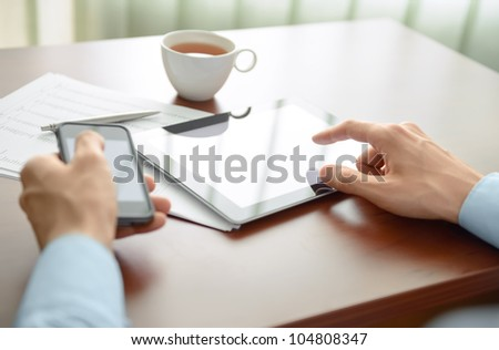 Businessman working at his workplace and using new technologies for success workflow. - stock photo